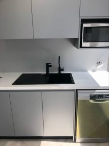 newly installed commercial kitchen with black tapwear, a microwave and dishwasher in white and grey cabinetry