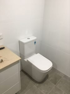 renovated bathoom with white walls, grey tiles floors and a while toilet.